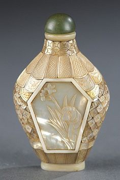 A Chinese snuff bottle. Late 19th century. Mother-of-pearl with floral designs…