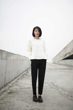 short bob, red lips, white sweater, black slacks