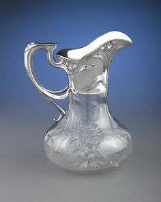 This graceful and intricate cut glass pitcher, mounted in Gorham sterling silver, is adorned with a dramatic daffodil motif, executed with the greatest skill and artistry. This naturalistic design, a hallmark of Art Nouveau, is cut with great intricacy into the pitcher's rounded body, and is echoed in the fine sterling silver collar and handle. With its organic shape and stunning three-part handle, this pitcher is an exquisite work of Art Nouveau elegance. Excellent condition.Silver co…