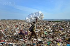 An Indonesian scavenger collects items from a garbage dump in Denpasar on the…