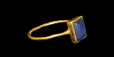 MEDIEVAL GOLD RING WITH BLUE GLASS SETTING 13th-14th century AD  A fine round-section hoop with rectangular cell bezel, blue glass pyramidal insert. 3.59 grams, 27 mm overall, 20.70 mm internal diameter