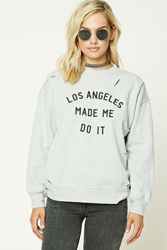 """A fleece knit sweatshirt featuring distressed, raw cutouts, a front """"Los Angeles Made Me Do It"""" graphic, a round neckline, long dolman sleeves, and ribbed knit trim."""