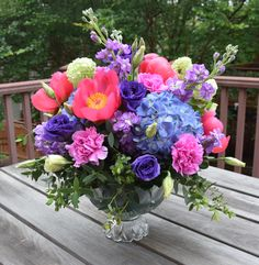 Large table flower arrangement for Mother's Day. Coral peonies, purple hydrangeas, stock, lisianthus, carnations, viburnum.