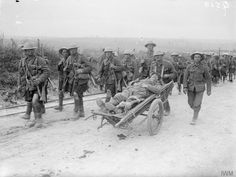 Troops of the Gordon Highlanders regiment on the Albert-Bapaume road near Ovillers, July 1916. Note the German prisoner being transported on a wheeled stretcher.