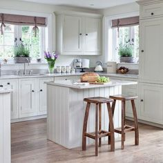 Love this small white cottage farmhouse kitchen.  The gray countertops give a little offset to all the white and the curtain valances give a little pop of color.  Good use of a small island in this tiny kitchen.  See ALL white country kitchen pictures here: http://outintherealworld.com/home-kitchens-interior-design-white-cottage-farmhouse-kitchens-country-kitchen-designs-we-love/