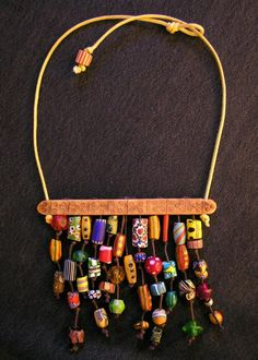 An antique bone divider from Tibet supports a wonderful variety of 42 mixed African trade beads from the early 1800s-1900s. On a waxed cotton cord with a trade bead closure.