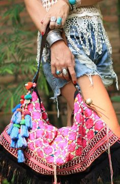 A gypsy style bohemian pink shoulder bag with tassels and pom pom's handmade in Thailand.