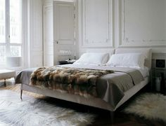 Elegant white bedroom, love the fur throw, rugs and panelling. Simple, clean and chic.