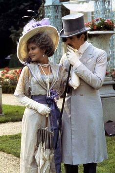 "Ornella Muti, wearing white opera gloves, with Jeremy Irons in dove gray from a still from their 1983 film ""Swann In Love"""