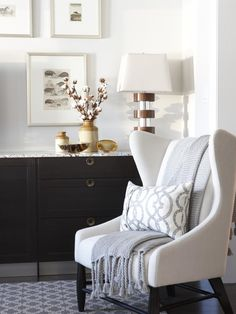 This white and gray color scheme features pops of color in brown from the lamp and decor and black in the marble top dresser giving this sitting area a defined elegance and cleanliness. The rug and wall art ties the room together making it cozy and restful. The patterned pillow and the gray throw complete the look.