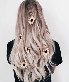 Natural blonde ombré and balayaged hair. Styled with loose curls and scattered sunflowers