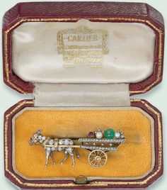 AN ART DECO DIAMOND AND GEM-SET NOVELTY BROOCH, BY CARTIER  Designed as a single-cut diamond donkey pulling a cart with revolving wheels and ruby, emerald and pearl provisions, mounted in silver and gold, pearls untested, circa 1925, 3.7 cm wide, in red leather Cartier case Signed Cartier London