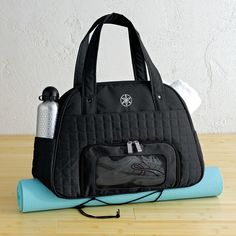 Our eco-chic Everything Fits Gym Bag keeps your essentials all in one place. Features an exterior zip pocket, an interior elastic pocket, key fob, and a vented exterior compartment for shoes, wet clothes, or a towel. Also includes an easy-reach exterior pocket for water bottle and interior pockets for cell phone and MP3 player. Conveniently attach your mat to the bottom with the adjustable straps. $48.00