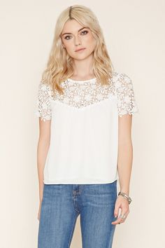 12 A short-sleeved woven top featuring a floral crochet paneled yoke with scalloped trim and a buttoned keyhole back.