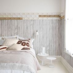 Scandinavian bedroom with wooden peg rails and wood-effect wallpaper