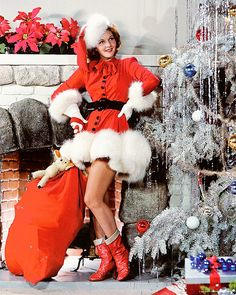 1943 - look at that awesome flocked & tinseled tree!!!  Broadway actress, Mary Martin shows off a saucy Santa's ensemble