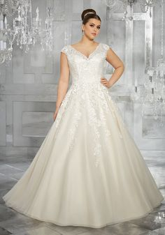 Breathtaking and Timeless, this Tulle Bridal Ball Gown Features Frosted, Embroidered Appliqués and an Off-the-Shoulder V-Neckline with Cap Sleeves. Colors Available: White, Ivory, Ivory/Light Gold.