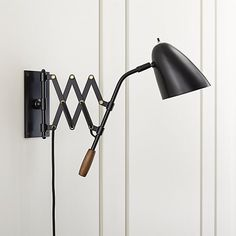 Shop Morgan Black Sconce.  A pull on the warm wood handle stretches the scissor arm of our retro-modern sconce right where it's needed.  Task-style lighting comes to you in sleek black-finished steel and moves back again as a room-illuminating sconce.