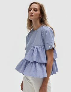 Contemporary top from Farrow in Blue-and-White stripe. Round neckline. Back button closure with keyhole detail. Short sleeves with pin and bauble detail. Tiered ruffles. Flared silhouette. Casual fit.  • Poplin • 65% polyester, 35% cotton • Hand wash