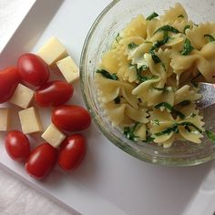 Pasta with leafy greens, grape tomatoes, and cheese cubes.