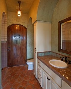 Rustic Tuscan Spanish hacienda. Love the rough texture door and smooth shiny tile sink