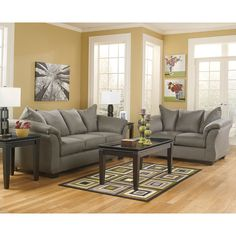 With the exciting contemporary style of the sweeping padded arms and plush pillow back design, the sleek beauty of the Darcy - Cobblestone Living Room Set by Signature Design by Ashley Furniture is sure to awaken the decor of any home environment while offering the comfort that you have been searching for.