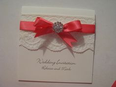 Vintage wedding invitation with lace, satin ribbon and a crystal diamante embellishment. Shown in coral