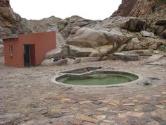 Riemvasmaak Hot Springs - Northern Cape - South Africa. This wild landscape was formed by volcanic activity millions of years ago but it's all pretty quiet now. Its main attraction, aside from the mountain desert and wilderness which offers exciting photographic opportunities, is the hot springs. These are surrounded by 80m granite cliffs, about as stark a setting as you can get — it also helps to set off the color of the water.
