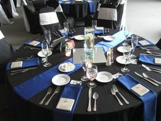 Royal Blue Satin Table Runner and Napkins accent the Black Table Linen, Black Chair Covers, and White Chair Sashes