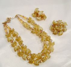This Vendome parure features unique honey gold givre glass beads, translucent beads, and Swarovski topaz crystals to stunning effect. The double strand necklace is comprised of these wonderful curved givre beads stacked in twos. Between these beads are translucent round gold-beige beads, and Swarovki AB topaz faceted crystals. The necklace has a maximum wearable length of 17 1/2 inches which includes the 2 inch crystal bead chain. The necklace has the signed J-hook and the metal…