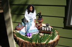 Coffee Ceremony doll and scene including coffee pot, cups, tray, basket, popcorn, grass, stool, coffee roaster and coal burner on a wooden