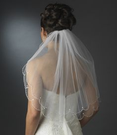 Add the perfect touch to your wedding outfit with this double tier veil featuring a scalloped edge of embellishment! This wedding accessory highlights a pencil style edge that is illuminated with components of Faux Pearls, sequencing and Austrian crystals.   Waist Length Veil with