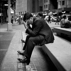 A businessman massages his temple as he talks outside the New York Stock Exchange in Manhattan, New York, on September 18, 2008. - Ashley Gilbertson