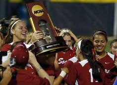 Oklahoma's Keilani Ricketts, left, holds the championship trophy after Oklahoma defeated Tennessee in the second game of the best of three Women's College World Series NCAA softball championship series in Oklahoma City, Tuesday, June 4, 2013. Oklahoma won the game 4-0 and the best of three series in two games.(AP Photo/Sue Ogrocki)