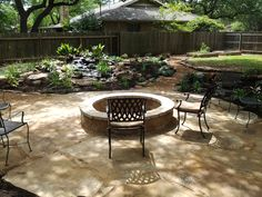 Oklahoma flagstone patio set in decomposed granite with fire pit and water feature set in a beautiful shade garden with herb planters in the sun.