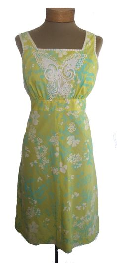 An kitschy  vintage 1960s Lilly Pulitzer dress  is perfect for when the weather turns warm. The  vintage designer dress  will brighten your day! The fabric has a yellow background with white flowers and mint green petals and leaves. Lilly written in print.  In the front center of this  vintage dress  there is a large white lace applique butterfly which is the focal point of the dress. The style of...