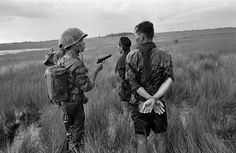 Shot by the Associated Press photographer Horst Faas, a South Vietnamese soldier holds a cocked pistol as he questions two suspected Viet Cong guerrillas captured in a weed-filled marsh in the southern delta region Vietnam History, Vietnam War Photos, American War, American History, American Veterans, Colt M1911, North Vietnam, Crime, Vietnam Veterans