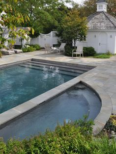 Pool with stone surround/decking and square lattice-topped fencing, wood shingled roof with cupola on dependency...evokes Colonial Williamsburg