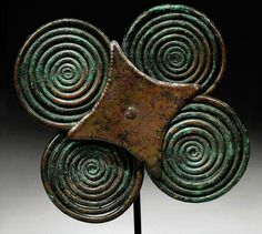 AN ITALIC BRONZE DOUBLE SPECTACLE FIBULA   CIRCA 8TH CENTURY B.C.   Composed of four interlocking spirals, with a four-pointed attachment plate with stippled border riveted through the centre to a bronze pin on the back, mounted  4¼ in. (10.8 cm.) diam. max.