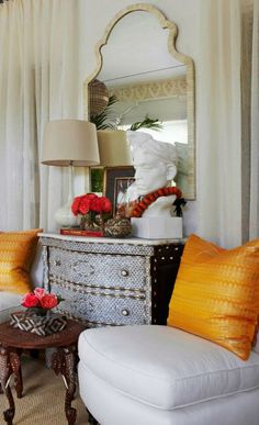 """Global Chic - Red Cross Palm Beach Showhouse   Traditional Home - """"Man in Turban,"""" a sculpture by Denis Lamarsh, serves as the curious focal point atop this impressive inlaid cabinet. Bursts of orange and cherry red add interest to the space."""