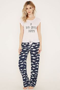 """This knit PJ set includes a tee with cap sleeves, a crew neckline, an """"I Do Not Bite"""" graphic on the front, and an open crisscross-cutout back, and a pair of woven pants with an elasticized drawstring waist and an allover shark print."""