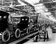 Body drop area in a Ford Model T plant. This is where the body drops from an overhead conveyer to be mated to a completed chassis. Even in these early years of automobile production Ford employed men to time study procedures to find and eliminate inefficiencies.