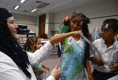 Librarian and storyteller Gregg Krispell, left, helps keep Bob the  Parrot on Remi Moslemi's shoulder while Diego Nocobe watches during a  pirate-themed event Wednesday at the Hilton Head Island library. The  7-year-olds learned about pirates, played games and walked away with eye  patches and paper swords. Wednesday was International Talk Like A  Pirate Day. |