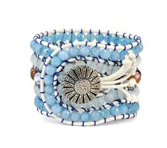 A 5 strands women's bracelet is handcrafted with semi precious stones of jade, agate multi colored & crystals of high quality. All of them are framed by natural white leather woven together with blue cotton cord. This statement design also features a metal, silver, vintage, lightly hammered, details button closure. This gorgeous bracelet pairs beautifully with other silver tone pieces, but can also make a subtle shimmering statement worn alone.