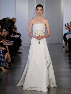 Peter Copping created an elegant outing for Oscar de la Renta Bridal's spring 2017 collection. Designing for the traditional bride, with modern touches in mind, the silhouette goes strapless and sleeveless with flared skirting. From a form-fitting mermaid silhouette to layered organza, the Oscar de la Renta bride is a fan of the bridal white …