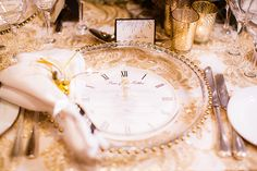 This classy table setting is timeless — literally. A menu printed on a paper clock fits elegantly into a transparent plate edged with gilded studs against a gold brocade tablecloth and paired with mercury candles.