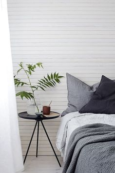 Linen bedding and lovely side-table in a delightful home in Finland.