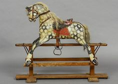 An early 20th century rocking horse Of typical form, with dapple grey painted decoration.  118 cm long.