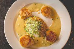 Four pan-seared jumbo sea scallops. Plated around a generous scoop of creamy mushroom risotto (garnished with fresh sprouts), smothered in a sweet pea and lobster cream sauce.