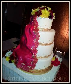Indian buttercream wedding cake with gold fondant, fresh flowers, and fondant handcrafted sari